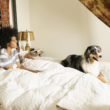 Mixed race woman sitting with dog in bed