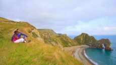 A couple sitting on the clifftop above Durdle Door on the Jurrassic coast of Dorset. The man is a right below knee amputee and the woman is profoundly deaf., Durdle Door, Dorset, England.  Additional Credit: Tourism For All
