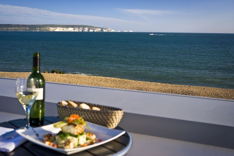Al fresco summer dining with seafood, white wine and coastal views