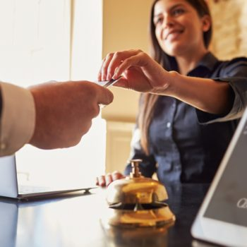 Guest takes room key card at check-in desk of hotel