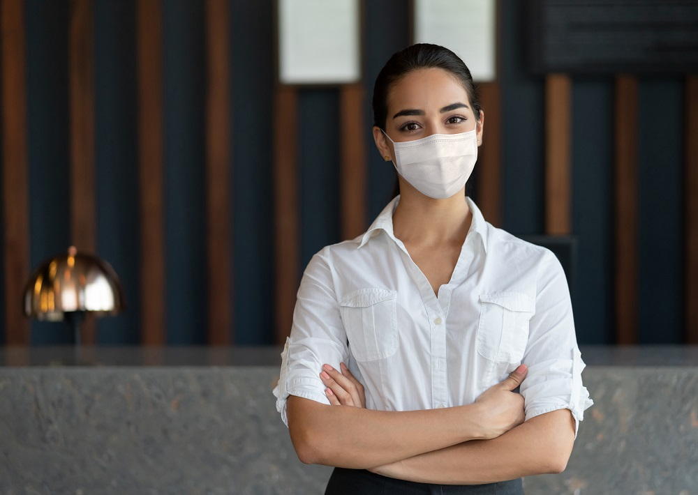 Woman working at the front desk of a hotel wearing a facemask